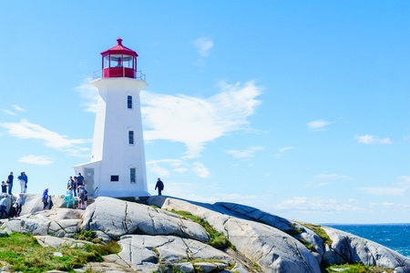 Peggys Cove, Canada - September 22, 2018: View of the lighthouse, with tourists, in the fishing village Peggys Cove, Nova Scotia, Canada