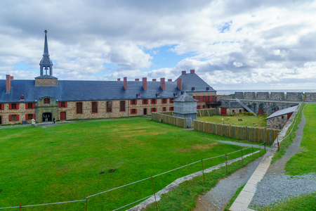 Louisbourg, Canada - September 20, 2018: Historic buildings in the fortress of Louisbourg, with visitors, Cape Breton island, Nova Scotia, Canada Editorial