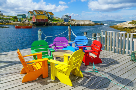 View of colorful chairs, boats and houses, in the fishing village Peggys Cove, Nova Scotia, Canada