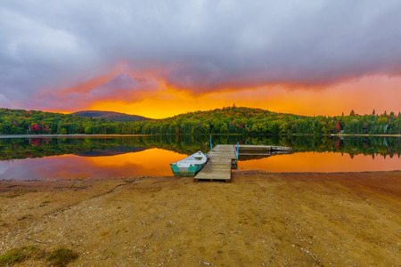 Boat and pier at sunset in Petit Lac Monroe, Mont Tremblant NP, Quebec, Canada