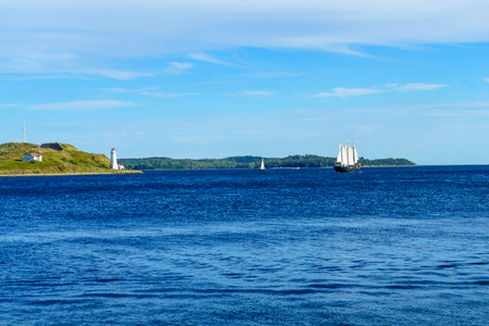 View of Georges Island lighthouse, and a sailboat, in Halifax, Nova Scotia, Canada Stock Photo