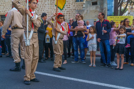 Haifa, Israel - April 27, 2019: Scouts perform a Holy Saturday parade, and crowd attend and hold the holy fire, part of Orthodox Easter celebration in Haifa, Israel Editorial