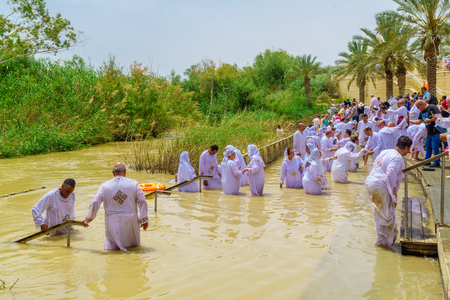 Qasr el Yahud, West Bank - April 24, 2019: Pilgrims baptize in Qasr el Yahud (Castle of the Jews), in the Jordan River. It is the traditional site of the baptism of Jesus by John the Baptist
