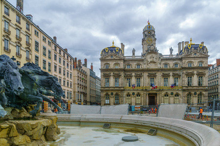 Lyon, France - May 09, 2019: The Terreaux square, the Bartholdi Fountain, and the City Hall building (Hotel de Ville), with construction workers, in Lyon, France