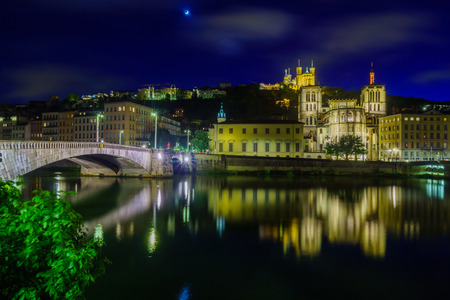 Night view of the Saone river, Bonaparte bridge, the Saint-Jean cathedral, and Notre-Dame basilica, in Lyon, France Stok Fotoğraf