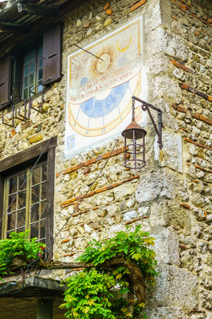 View of an old sun clock, in the medieval village Perouges, Ain department, France