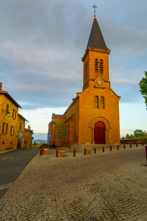 Village center and the church, at sunrise, in Moire, Beaujolais, Rhone department, France