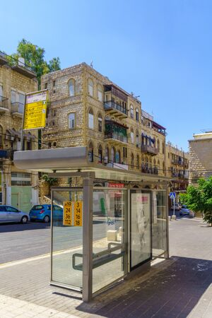 Haifa, Israel - August 22, 2019: View of bus stop and old-style buildings, in downtown Haifa, Israel