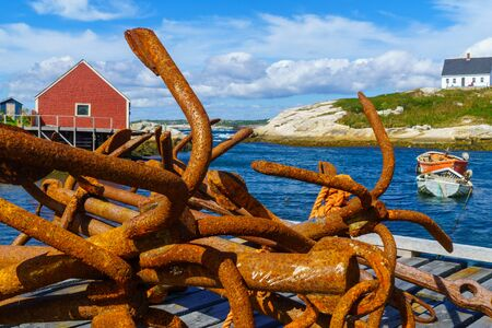 View of rusty anchors, boats and houses, in the fishing village Peggys Cove, Nova Scotia, Canada