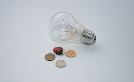tariff: Light bulb and coins on a white background Stock Photo