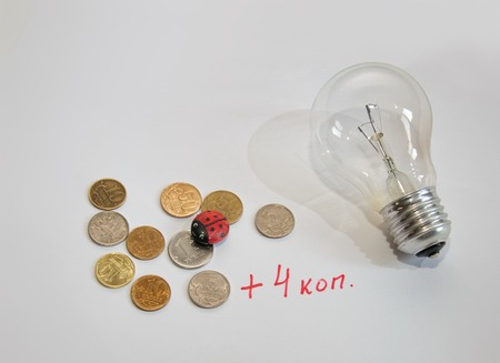 electricity tariff: Light bulb and coins on a white background Stock Photo