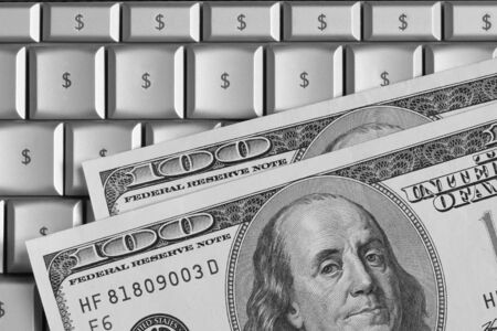 computer keys: US hundred dollar bills on top of a laptop. Keyboard characters replaced with dollar signs.