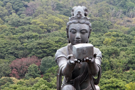 A Buddhistic statue making an offering to the Tian Tan Buddha in Hong Kong  photo