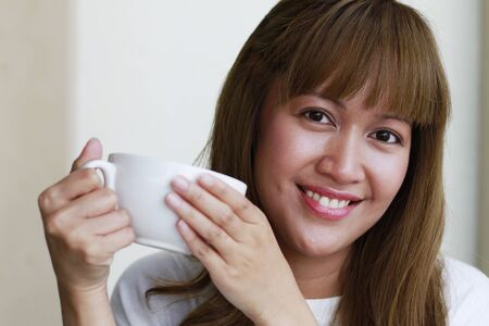 sipping: A young lady enjoying a hot cup of coffee