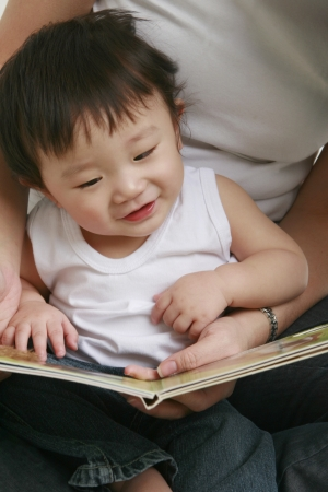 Cute toddler looking at a book photo