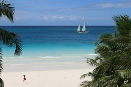 waters: The white sand beach of Boracay in the Philippines. Woman in photo not recognizable.  Stock Photo