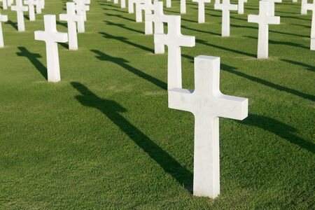 military cemetery: Crosses in a military cemetery with shadows on the green grass