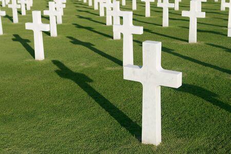 memorial cross: Las cruces en un cementerio militar con sombras sobre la hierba verde