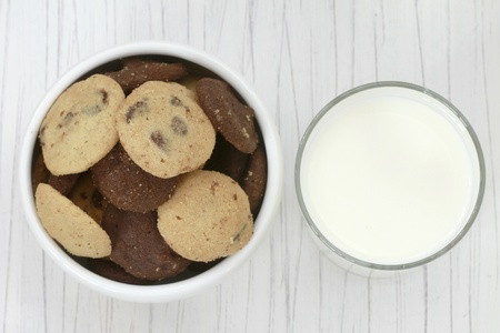 milk and cookies: Top view of a bowl of cookies and a glass of milk