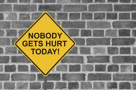 gets: A safety sign with a wall of an industrial workplace or factory building in the background