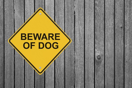 """beware: """"Beware of Dog"""" sign on a wooden fence"""