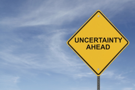 """Uncertainty Ahead"" sign on a blue sky with clouds background"