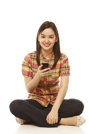 A young beautiful woman with a mobile phone looking at the camera  on white photo