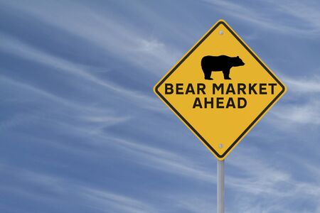 A modified road sign warning of a Bear Market Ahead on a blue sky as background photo