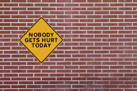 gets: Nobody Gets Hurt Today  - Safety reminder on a red brick wall of a factory building  Stock Photo