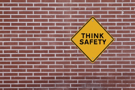 think safety: Think Safety  - Safety reminder on a red brick wall of a factory building