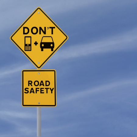 Modified road sign highlighting the danger of texting and driving  against a blue sky background   photo