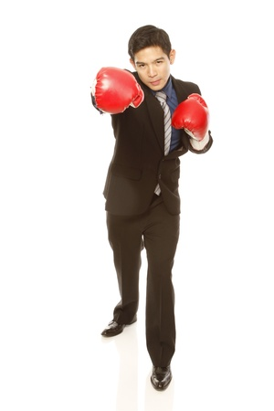 the fittest: Man in business attire wearing boxing gloves and throwing a punch (on white)  Stock Photo