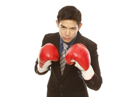 stance: Man in business attire wearing boxing gloves and in a fighting stance (on white)