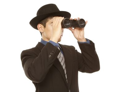 A man in business attire and hat using binoculars (on white) photo