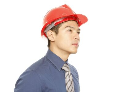 A man wearing a hard hat dreaming or contemplating (on white)  photo