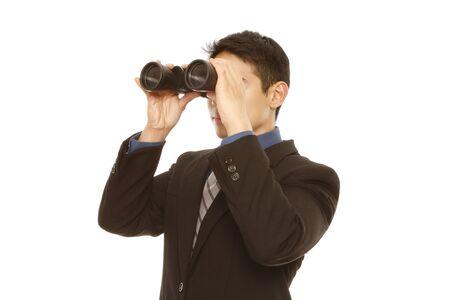A man in business attire using binoculars  on white   photo