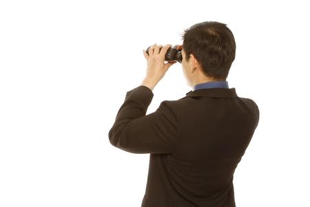 Achteraanzicht van een man in zakelijke kleding behulp van een verrekijker (op wit)