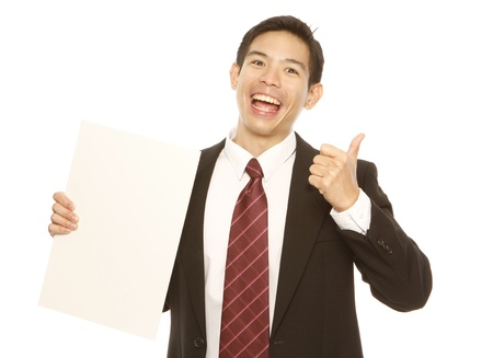 A businessman doing a thumbs up and holding a blank sheet  isolated on white   photo