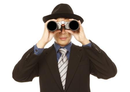 Een man in zakelijke kleding en hoed behulp van een verrekijker (op wit)