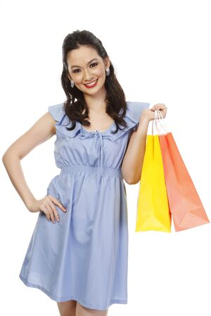 An attractive fashionable woman holding colorful paper shopping bags  isolated on white   photo
