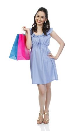 Een aantrekkelijke modieuze vrouw met kleurrijke papieren boodschappentassen op wit wordt geïsoleerd Stockfoto