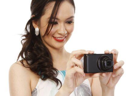 point and shoot: Una mujer joven de moda que sostiene un punto de disparar la c�mara con poca profundidad de campo se centra en la c�mara y aislado en blanco
