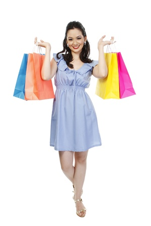 heeled: Full body shot of an attractive fashionable woman holding colorful paper shopping bags  isolated on white