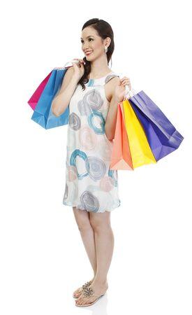 full body shot: Golpe al cuerpo completo de una mujer de moda atractiva sosteniendo coloridas bolsas de la compra de papel (aislado en blanco)