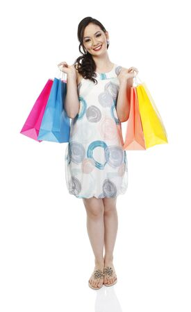 Full body shot of an attractive fashionable woman holding colorful paper shopping bags (isolated on white)  Stock Photo - 14796981