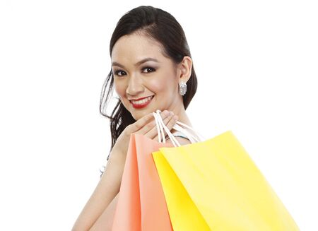 asian shopper: An attractive fashionable woman holding colorful paper shopping bags (isolated on white)
