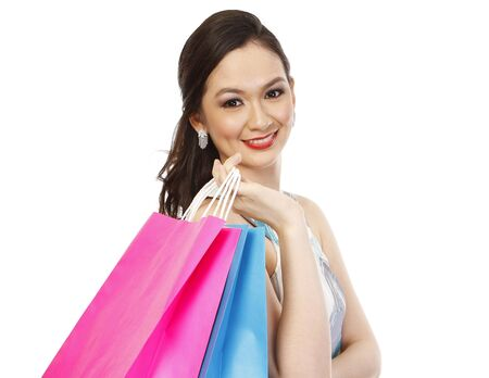 An attractive fashionable woman holding colorful paper shopping bags (isolated on white)  photo