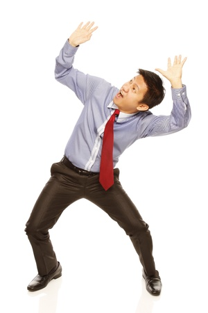 A man in shirt and tie acting afraid of being crushed on white background  Stockfoto