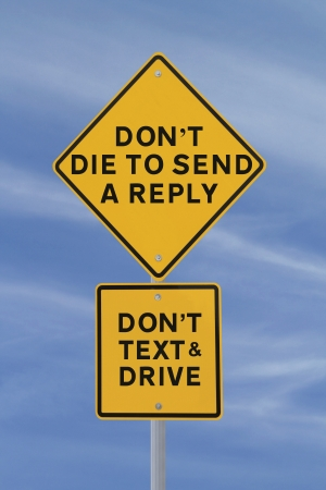 Amusing road sign warning of the danger of texting and driving  against a blue sky background   photo