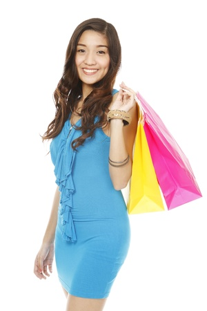 An attractive young woman holding paper shopping bags  isolated on white   photo